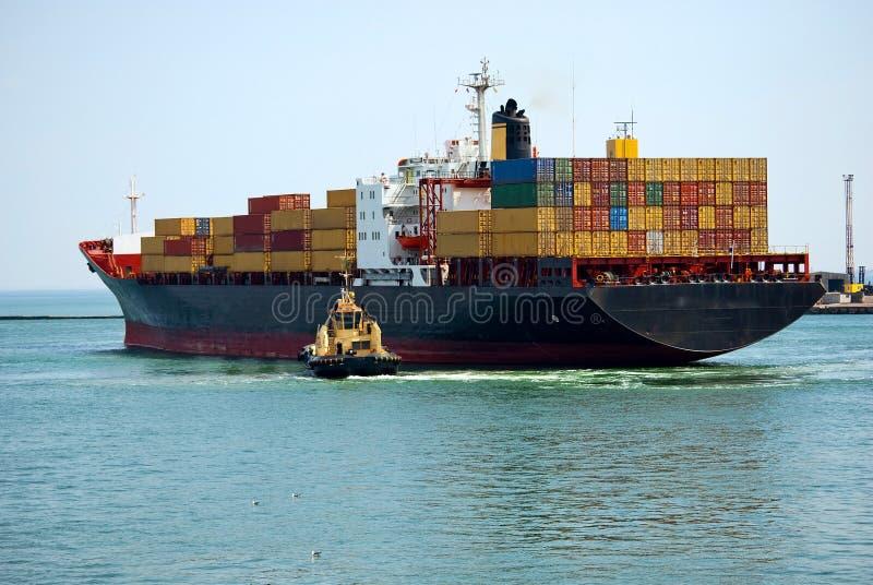 Il piccolo rimorchiatore vicino alla grande nave fotografia stock libera da diritti