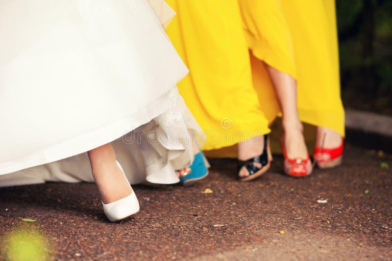 Il piede della sposa in scarpe ed in damigelle d'onore immagine stock libera da diritti