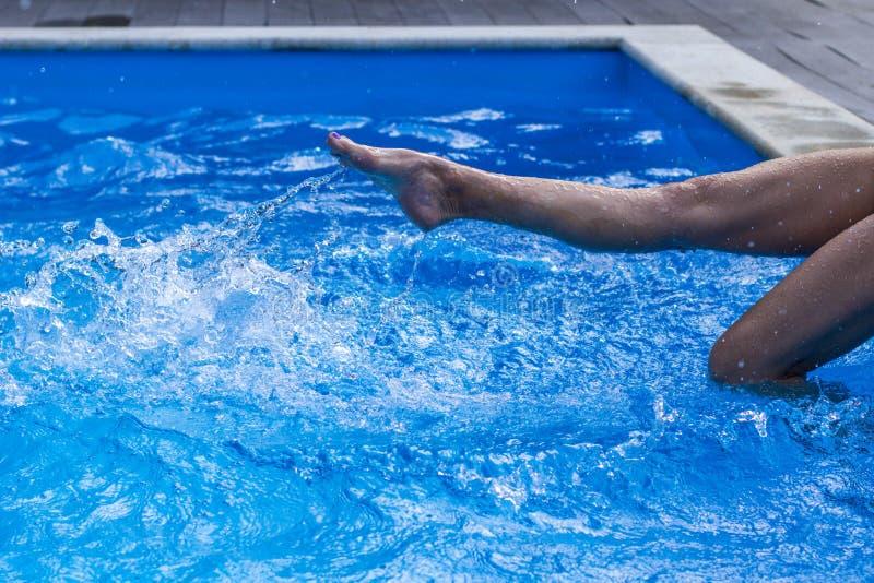 Il piede delle giovani donne nella piscina dell'acqua, spruzza dalle gambe femminili immagine stock libera da diritti