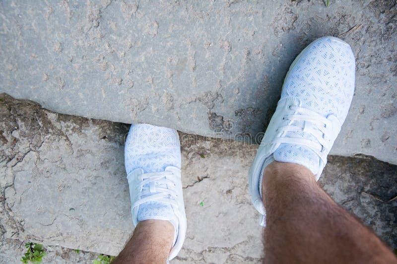 Il piede di un uomo nei supporti bianchi delle scarpe da tennis sui punti di pietra di estate Camminando nelle scarpe immagine stock libera da diritti
