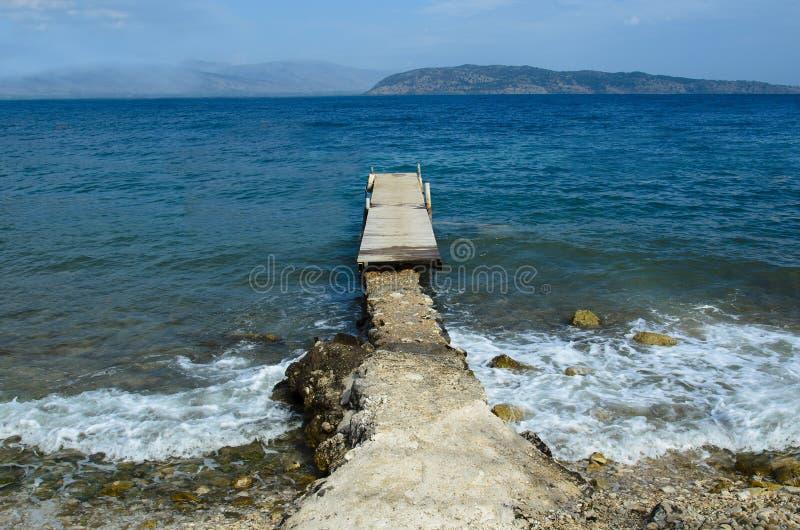 Il pilastro di legno collegato da un passaggio concreto sul fondo là è isole nel mare là è nessuno immagine stock