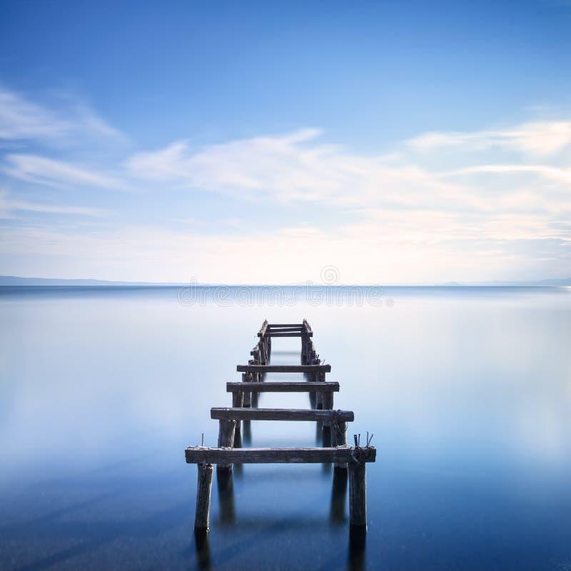 Il pilastro o il molo di legno rimane su un lago blu. Esposizione lunga. fotografia stock