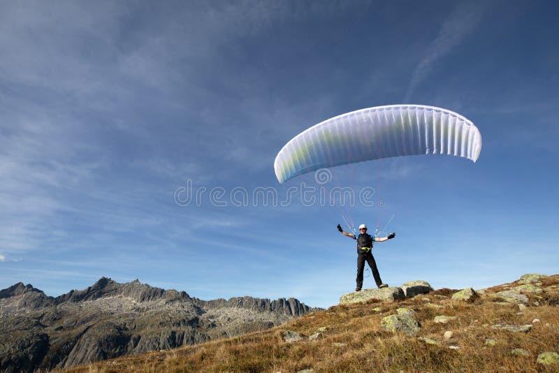 Il pilota dell'aliante sta su una roccia ed equilibra il suo aliante sopra la sua testa vicino al lago Grimsel nelle alpi svizzer fotografia stock libera da diritti
