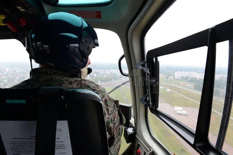 Il pilota di un elicottero di polizia, Eurocopter COME 355 nel cielo sopra la città immagini stock