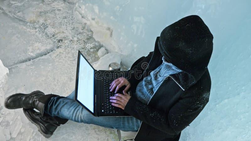 Il pirata informatico incide il server Uomo da programmare sul computer portatile in caverna di ghiaccio Intorno alla grotta mist fotografia stock libera da diritti