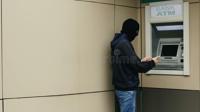 Il pirata informatico o il ladro con lo smartphone ruba le informazioni o i dati dal BANCOMAT della banca immagine stock