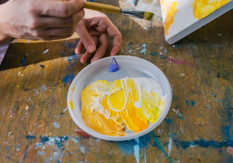 Il pittore in suo misto di colore del pennello della tenuta della mano pittura ad olio per pittura sulla tavolozza closeup immagini stock libere da diritti