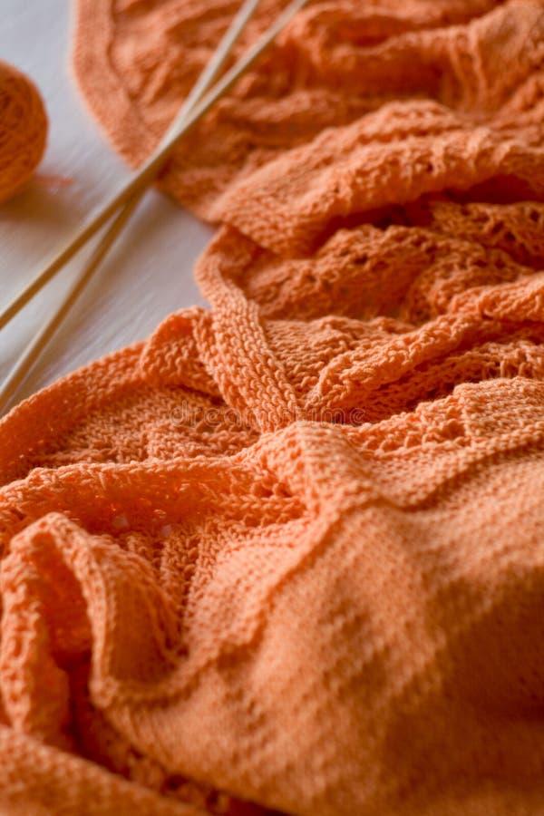 Il plaid arancio luminoso ha tricottato, ferri da maglia e palle del filato immagini stock