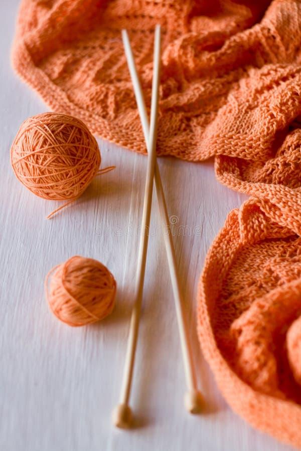 Il plaid arancio luminoso ha tricottato, ferri da maglia e palle del filato fotografie stock libere da diritti