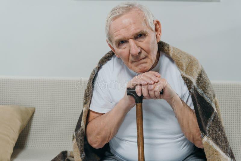 Il plaid d'uso dell'uomo senior si appoggia una canna mentre si siede immagini stock libere da diritti
