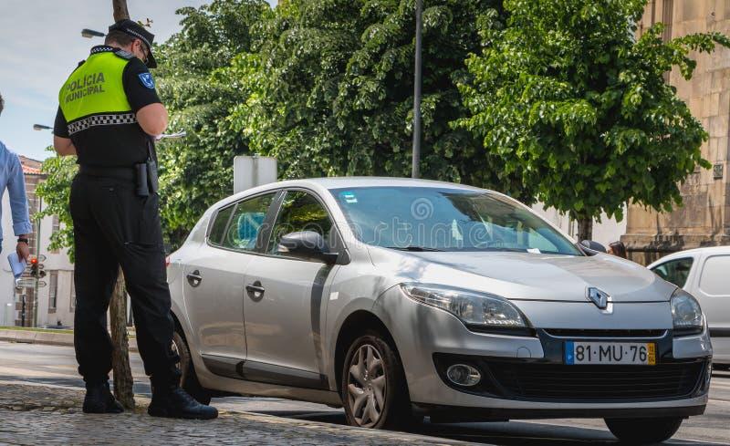 Il poliziotto controlla e scrive un biglietto di traffico fotografie stock