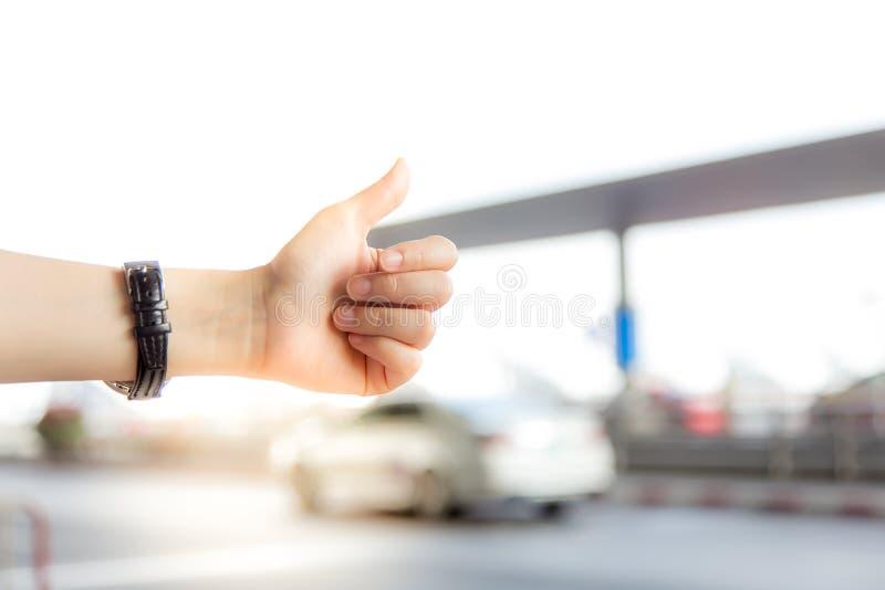 Il pollice su è il simbolo o il segno di aiuto o favore o hitchhike per immagini stock