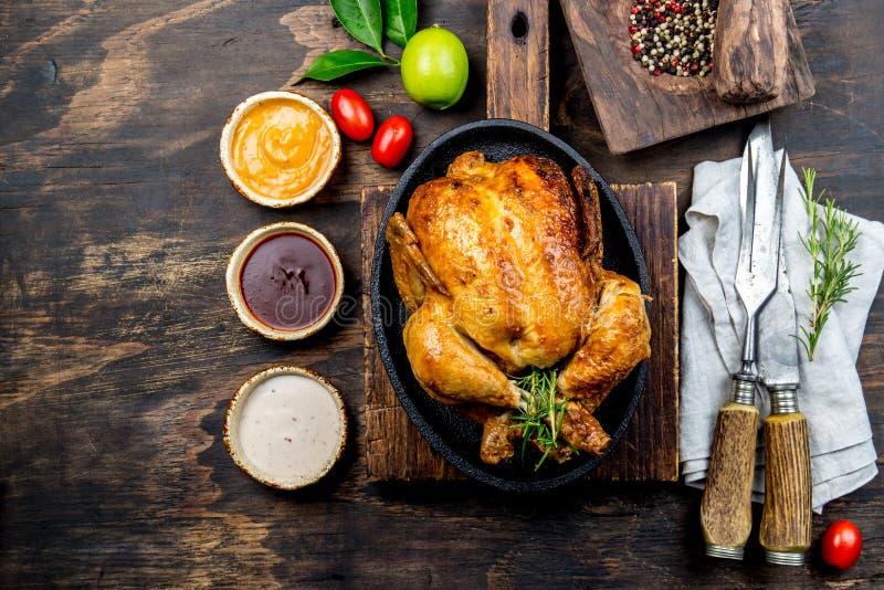 Il pollo arrostito con i rosmarini è servito sulla banda nera con le salse sulla tavola di legno, vista superiore immagini stock