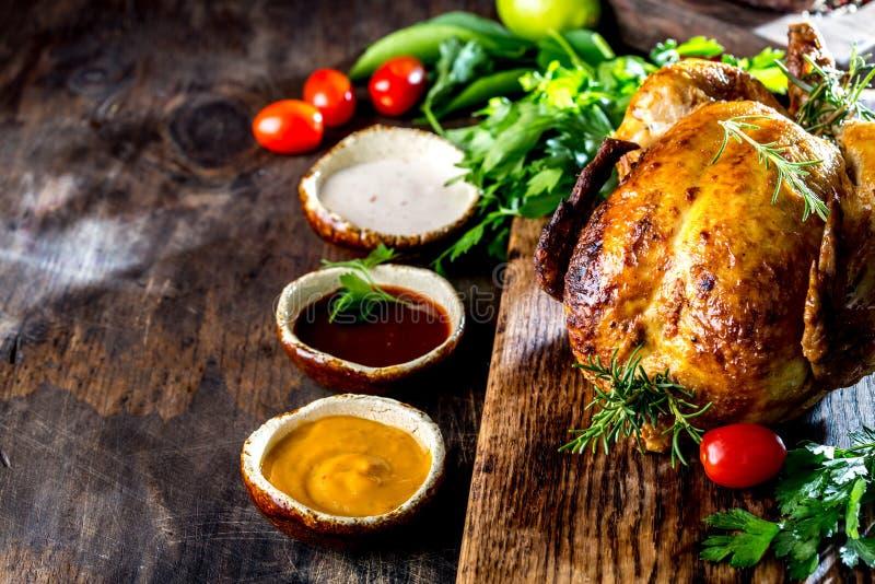 Il pollo arrostito con i rosmarini è servito sulla banda nera con le salse sulla tavola di legno, vista superiore immagine stock