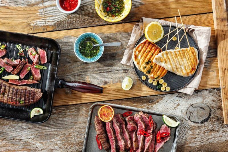 Il pollo del manzo della tavola di cena ha grigliato la vista superiore dell'alimento della carne all'aperto fotografia stock