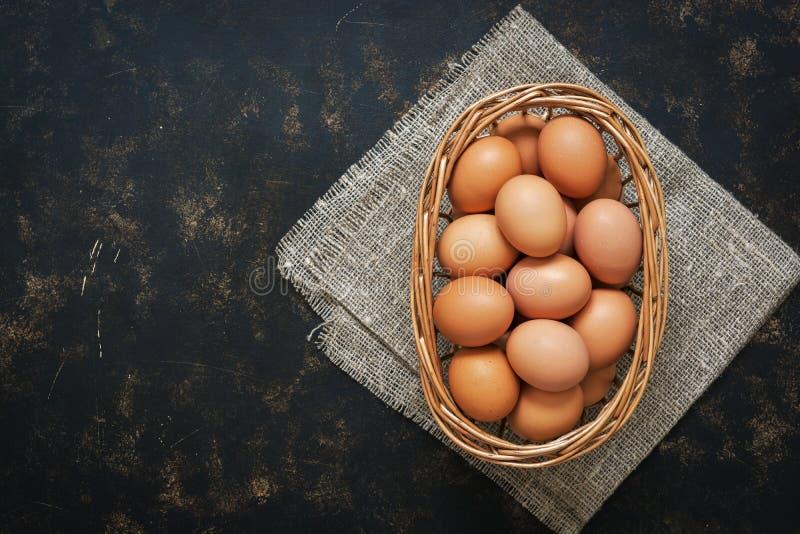 Il pollo di Brown eggs in un canestro su un fondo rustico scuro, lo spazio della copia, vista superiore fotografia stock libera da diritti