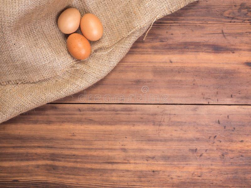 Il pollo eggs sui vecchi piani di appoggio di legno rurali e sul fondo d'annata della tela da imballaggio, vista superiore della  immagine stock