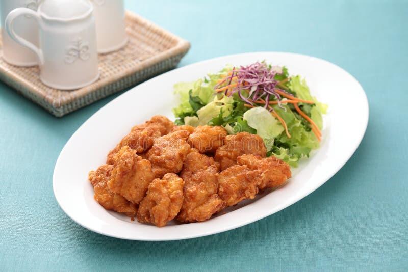 Il pollo fritto di Sunsal prende Ake con insalata sul piatto bianco con tè immagini stock libere da diritti