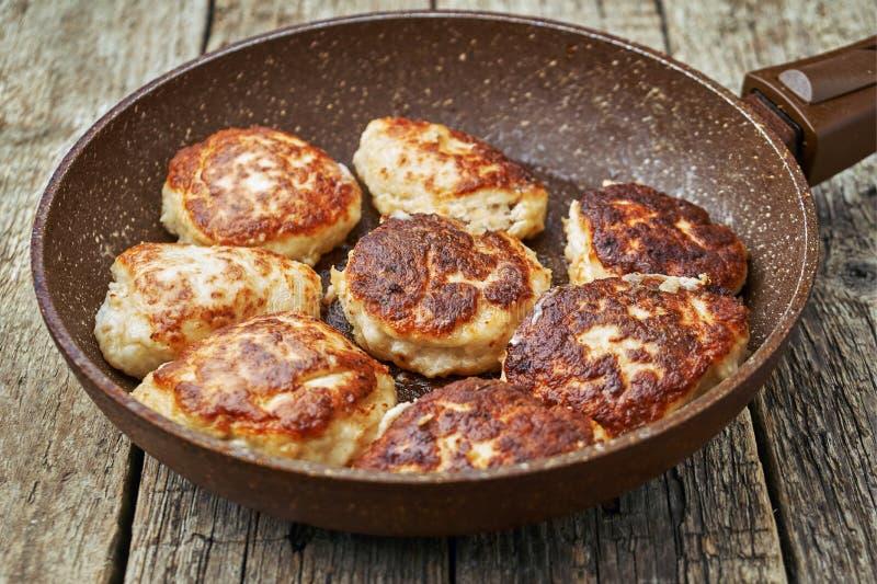 Il pollo ha fritto le cotolette nella pentola con un rivestimento di pietra sui bordi di legno immagini stock