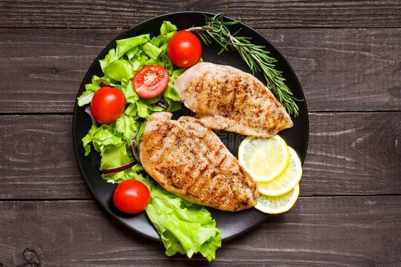 Il pollo ha grigliato il filetto con le erbe, le verdure ed il limone immagine stock
