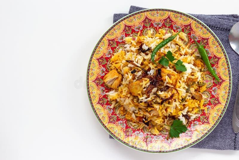 Il pollo indiano halal Biryani ? servito con il raita del pomodoro del yogurt sopra fondo bianco Fuoco selettivo Vista superiore immagini stock libere da diritti