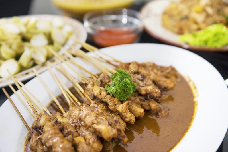 Il pollo saporito satay è servito con altri alimenti immagini stock