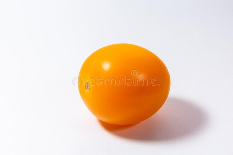 Il pomodoro ciliegia giallo si trova su un fondo bianco fotografie stock libere da diritti