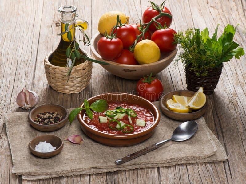 Il pomodoro freddo spagnolo ha basato la zuppa di verdure fredda della minestra servito in un piatto dell'argilla fotografie stock