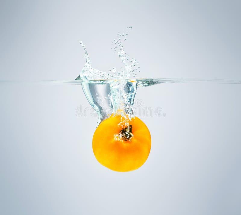 Il pomodoro giallo cade nell'acqua che sparge molti spruzzi e gocce fotografia stock libera da diritti