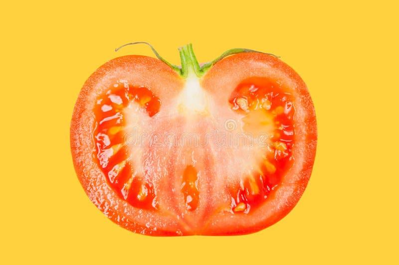 Il pomodoro levita in aria su fondo pastello giallo fotografia stock