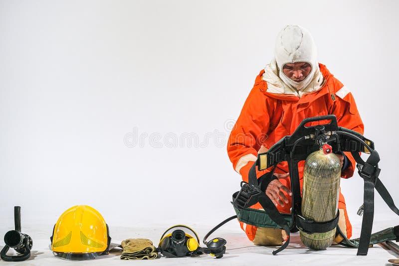 Il pompiere fa una dimostrazione dei caschi d'uso delle uniformi e di varie attrezzature per preparare i pompieri su un fondo bia fotografia stock libera da diritti