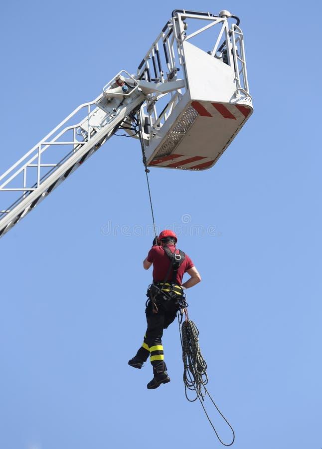 Il pompiere ha appeso la corda che scala nei pompieri immagini stock libere da diritti