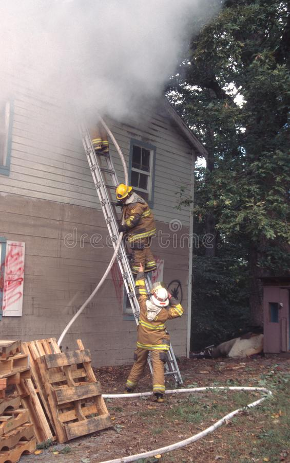 Il pompiere prende una linea di tubo flessibile al secondo piano di una casa su fuoco immagine stock libera da diritti