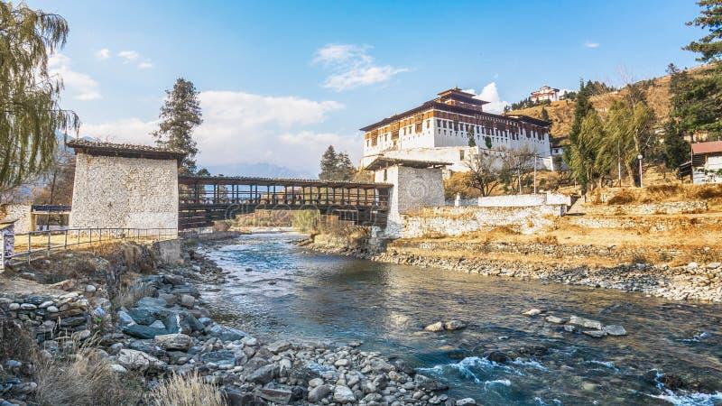Il ponte attraverso il fiume con il palazzo tradizionale del Bhutan immagini stock