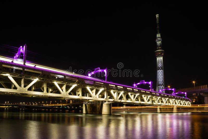 Il ponte ferroviario di Tobu sopra il fiume di Sumida si ? acceso nella porpora sotto Tokyo illuminata Skytree alla notte immagine stock