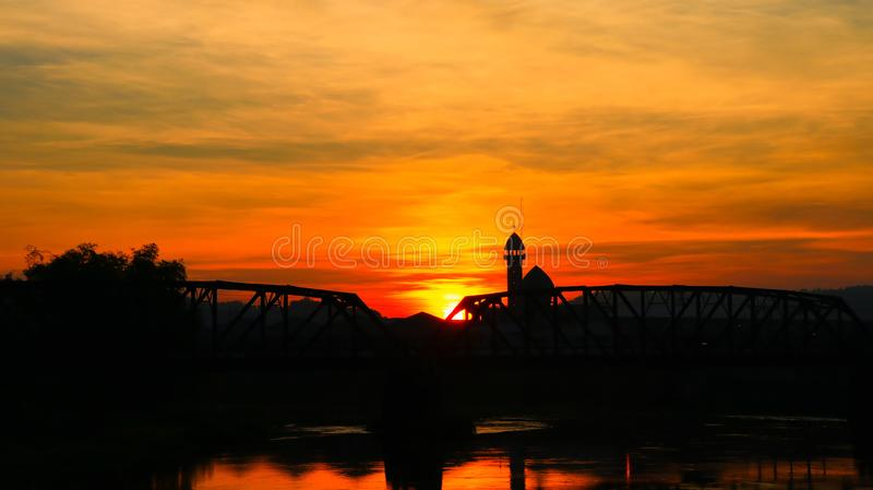 Il ponte ferroviario ed il riflesso della siluetta in fiume con l'alba nel rosso del cielo con lo spazio della copia aggiungono f fotografie stock