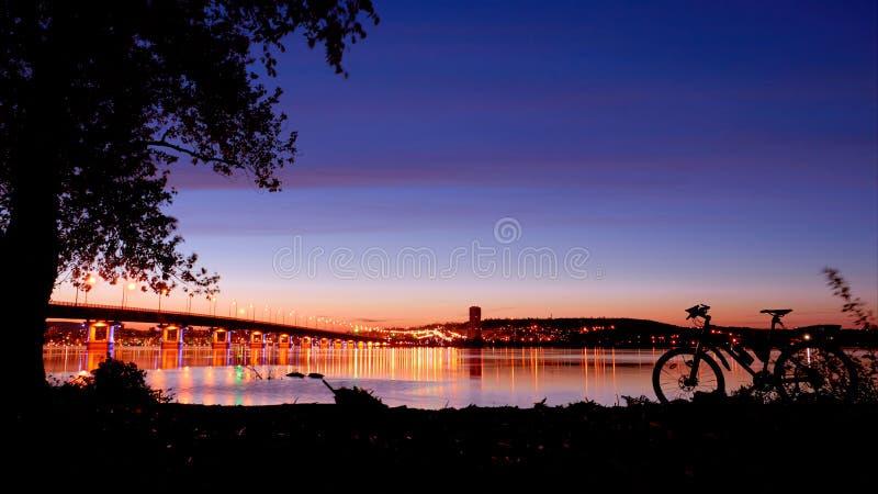 Il ponte sopra il fiume Volga e la bicicletta sulla riva fotografie stock libere da diritti