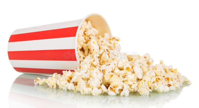Il popcorn è stato sparso dalla grande scatola a strisce, isolata su bianco fotografia stock libera da diritti