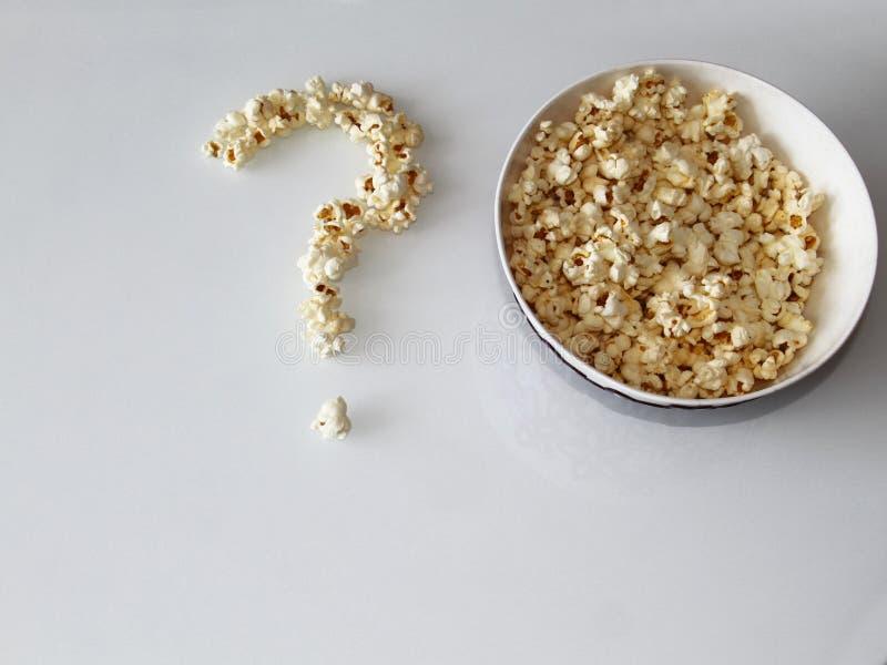 Il popcorn ha presentato sotto forma di domanda su un fondo bianco immagini stock