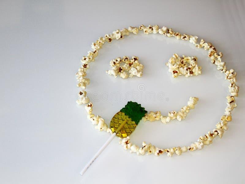 Il popcorn ha presentato sotto forma di uno smiley, su un fondo bianco immagine stock libera da diritti