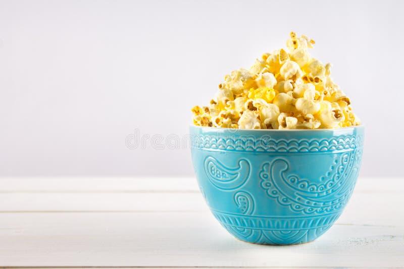 Il popcorn salato in una tazza blu è su una tavola di legno fotografia stock