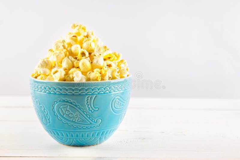 Il popcorn salato in una tazza blu è su una tavola di legno fotografie stock