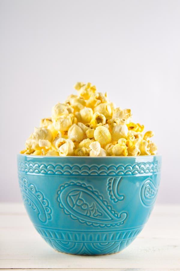 Il popcorn salato in una tazza blu è su una tavola di legno immagine stock