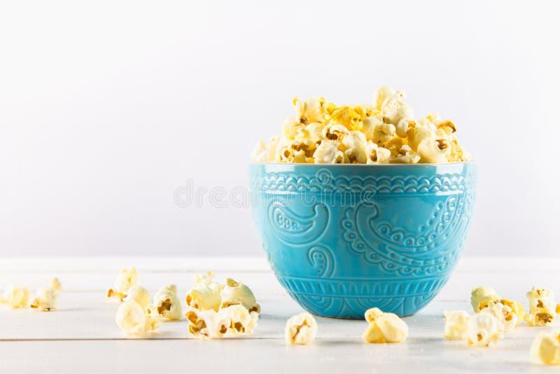 Il popcorn salato in una tazza blu è su una tavola di legno Il popcorn si trova intorno alla ciotola fotografia stock