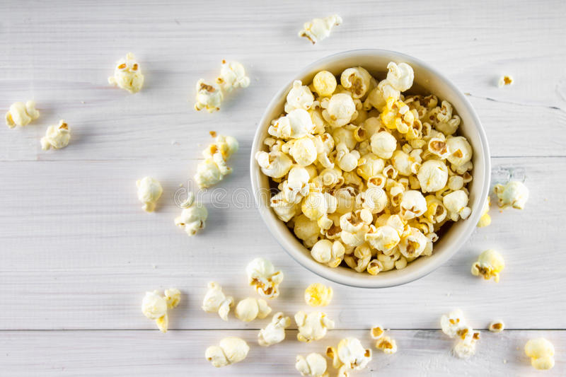 Il popcorn salato in una tazza blu è su una tavola di legno Il popcorn si trova intorno alla ciotola Vista superiore immagine stock libera da diritti