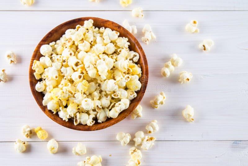 Il popcorn salato in una tazza di legno è su una tavola bianca Il popcorn si trova intorno alla ciotola Vista superiore immagine stock