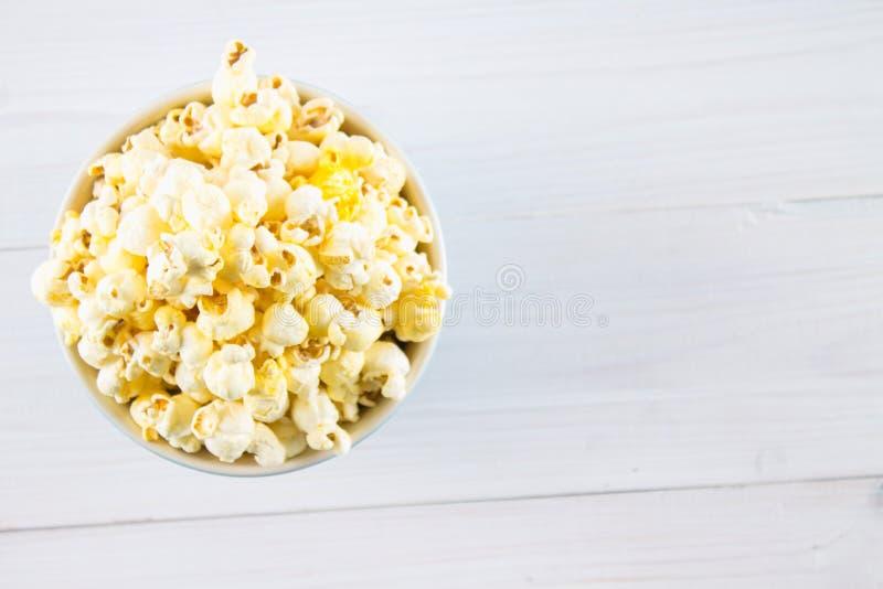 Il popcorn salato in una tazza di legno è su una tavola bianca Il popcorn si trova intorno alla ciotola Vista superiore fotografia stock libera da diritti