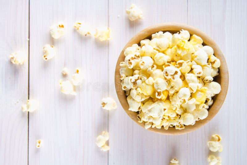 Il popcorn salato in una tazza di legno è su una tavola bianca Il popcorn si trova intorno alla ciotola Vista superiore fotografia stock