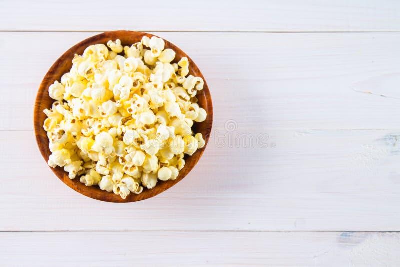 Il popcorn salato in una tazza di legno è su una tavola bianca Il popcorn si trova intorno alla ciotola Vista superiore immagini stock libere da diritti