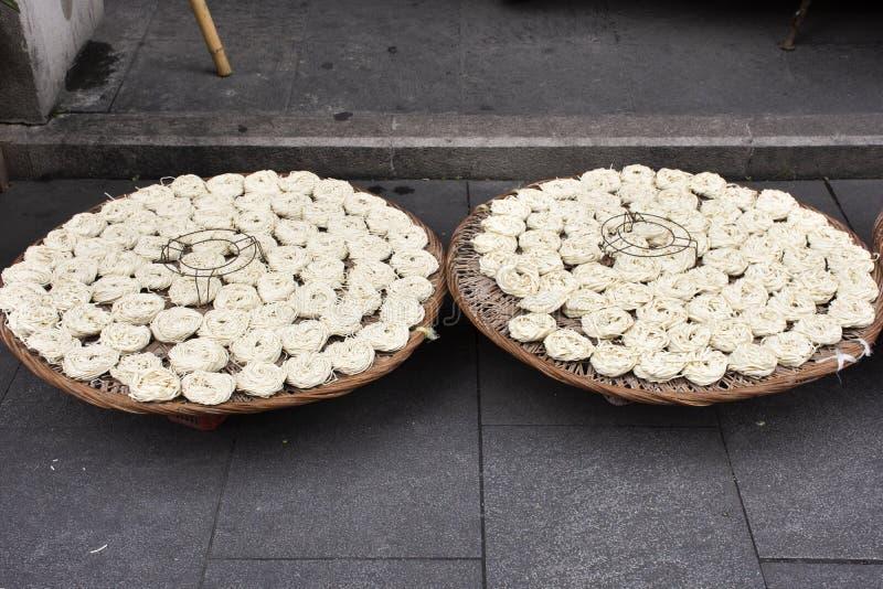 Il popolo cinese ha prodotto a tagliatella le tagliatelle asciugantesi casalinghe dell'uovo all'aperto su tessuto o sul canestro  immagini stock